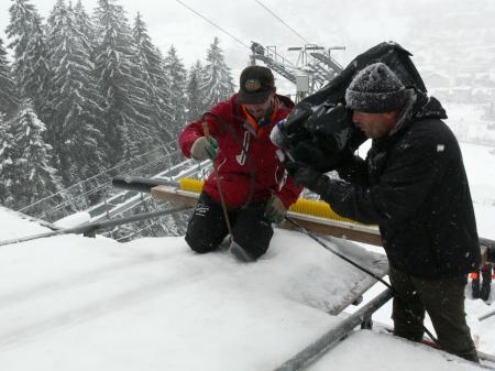 Beobachtet von einer Fernsehkamera bewässert Paul Töngi vom Schanzenteam den Absprungbalken der Titlis-Schanze. Bild Beat Christen